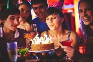 group of people at a party with birthday cake